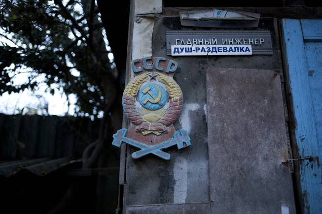 "In this photo taken on Wednesday, Nov. 27, 2013, the colored state emblem of the USSR hangs on the door of the outhouse in the yard of the railroad house in the village of Vesyoloye outside Sochi, Russia. Signs read ""Chief engineer; Showers."""