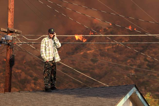 A resident on the roof of a house talks on the phone as a wildfire burns in the hills just north of the San Gabriel Valley community of Glendora, Calif. on Thursday, Jan 16, 2014. Southern California authorities have ordered the evacuation of homes at the edge of a fast-moving wildfire burning in the dangerously dry foothills of the San Gabriel Mountains.