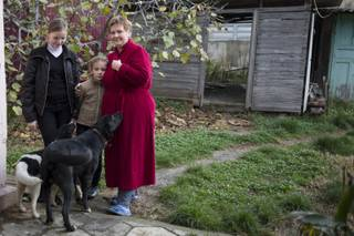 In this photo taken on Wednesday, Nov. 27, 2013, Alexandra Krivchenko, right, and her children, center, play with the dogs in the yard of a house sandwiched between the railway and a federal highway (seen in the background) in the village of Vesyoloye outside Sochi, Russia.