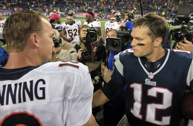 In this Oct. 7, 2012, file photo, Denver Broncos quarterback Peyton Manning, left, and New England Patriots quarterback Tom Brady, right, speak in the middle of the field after the Patriots beat the Broncos 31-21 in an NFL football game in Foxborough, Mass.