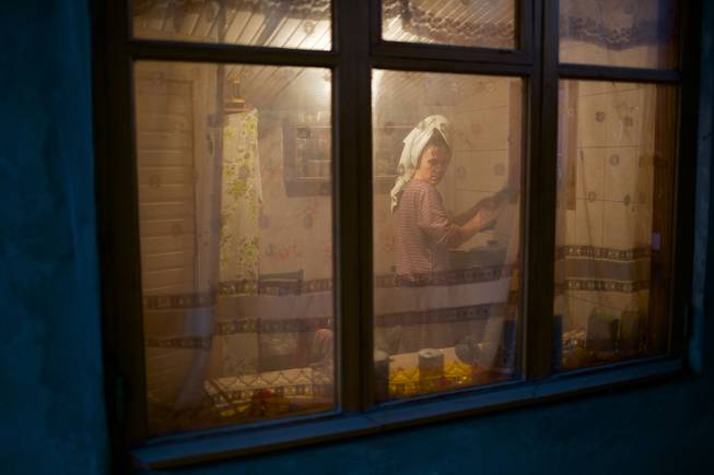 In this photo taken on Wednesday, Nov. 27, 2013, a woman washes up dishes in her kitchen in the yard of a house in the village of Vesyoloye, outside Sochi, Russia.