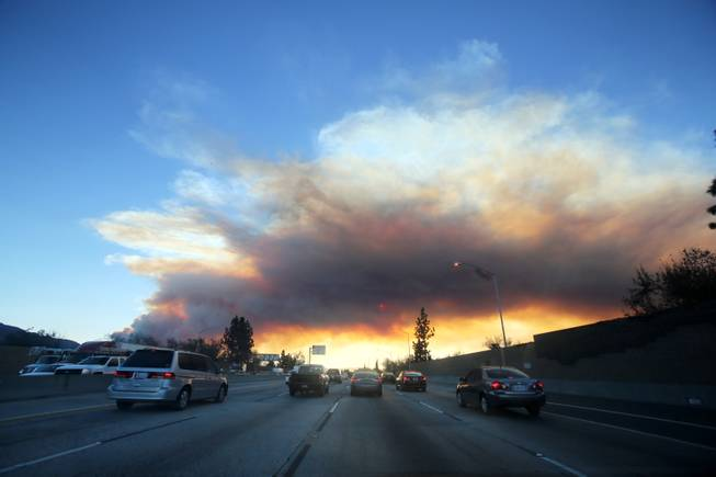 Commuters make their way along the 210 freewa as a wildfire burns in the hills just north of the San Gabriel Valley community of Glendora, Calif. on Thursday, Jan 16, 2014.