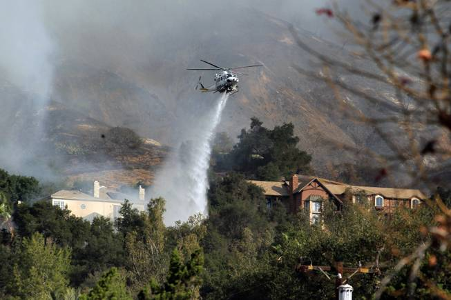 A firefighting helicopter makes a water drop over homes in Glendora, Calif. as a wildfire burns in the hills just north of the San Gabriel Valley community on Thursday, Jan 16, 2014.