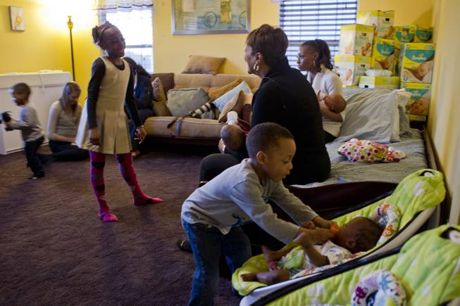 Derrick Derrico, 3, gives a pacifier to one of his quintuplet siblings as the family hangs out in the nursery Friday, Dec. 17, 2013.