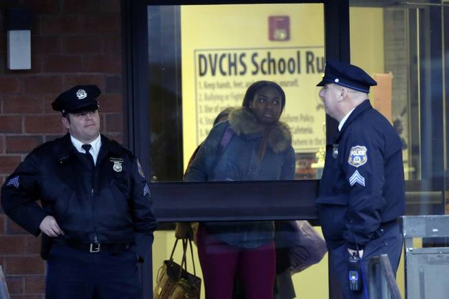 Studenta leave the Delaware Valley Charter School Friday, Jan. 17, 2014, in Philadelphia. Police say two students have been shot at a Philadelphia high school.