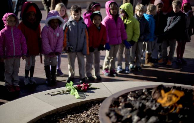 Roses sit in front of the eternal flame at the gravesite of Rev. Martin Luther King Jr., as kindergarten students with the Charles R. Drew Charter School pay a visit, Friday, Jan. 17, 2014, in Atlanta. The national Dr. Martin Luther King Jr. federal holiday this year is Monday, Jan. 20, five days after the civil rights leader would have turned 85-years-old.