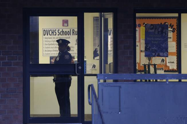 Police stands guard the Delaware Valley Charter School Friday, Jan. 17, 2014, in Philadelphia, after two students were shot by another student.