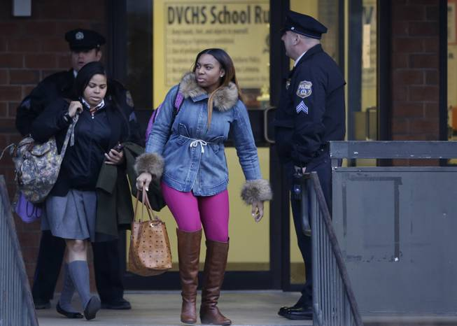 Students exit the Delaware Valley Charter School Friday, Jan. 17, 2014, in Philadelphia. Police say two students have been shot at a Philadelphia high school.