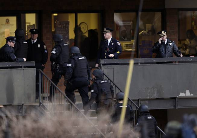 Police enter the Delaware Valley Charter School Friday, Jan. 17, 2014, in Philadelphia. Police say two students have been shot at a Philadelphia high school.