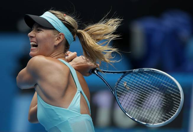 Maria Sharapova of Russia hits a backhand return to Alize Cornet of France during their third-round match at the Australian Open on Saturday, Jan. 18, 2014, in Melbourne, Australia.