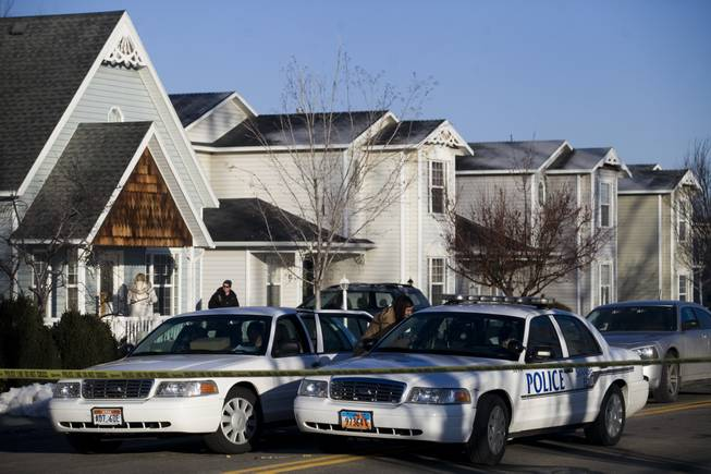 Police gather outside a home, Friday, Jan. 17, 2014, in Spanish Fork, Utah where five people were found dead on Thursday. A 34-year-old officer shot and killed his wife, mother-in-law and two young children and turned the gun on himself, authorities said Friday.