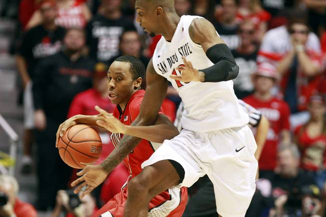 UNLV guard Kevin Olekabie is defended by SDSU Winston Shepard during their game Saturday, Jan. 18, 2014 at Viejas Arena in San Diego.