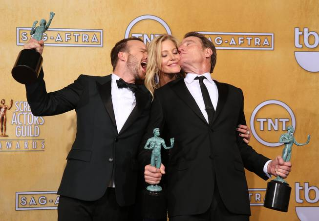 "Aaron Paul, Anna Gunn and Bryan Cranston pose in the press room with their awards for outstanding performance by an ensemble in a drama series for ""Breaking Bad"" at the 20th annual Screen Actors Guild Awards at the Shrine Auditorium on Saturday, Jan. 18, 2014, in Los Angeles. (Photo by Matt Sayles/Invision/AP)"