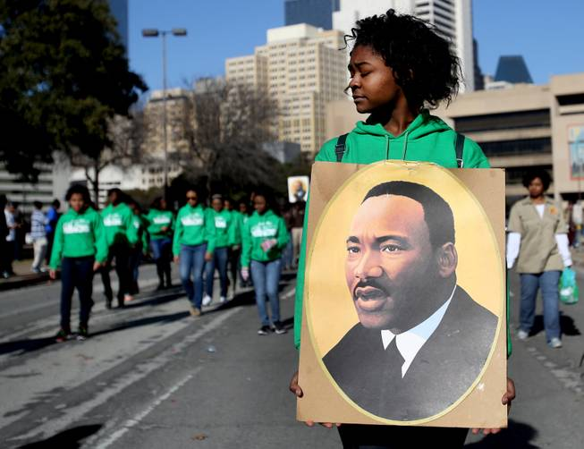 Sakidra Davis of Alpha Rho Xinos carries an image of Martin Luther King Jr. during the 32nd annual Martin Luther King Jr. Birthday Celebration's March/Parade on  Saturday Jan. 18, 2014,  in Dallas, Texas.