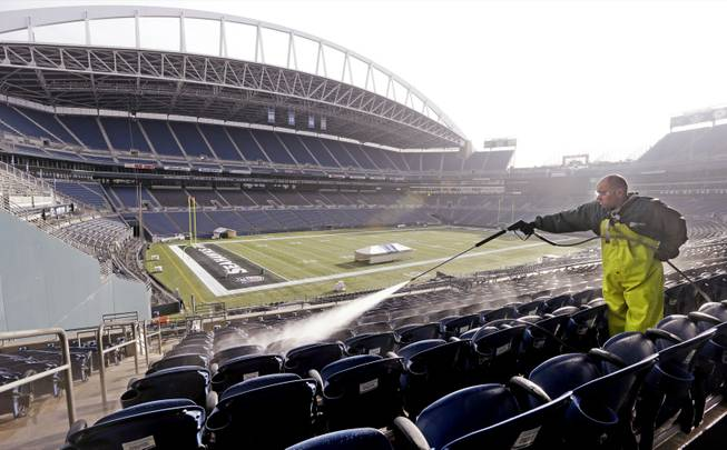 A worker cleans seats at CenturyLink Field on Wednesday, Jan. 15, 2014, in preparation for the NFL football NFC championship game Sunday in Seattle.