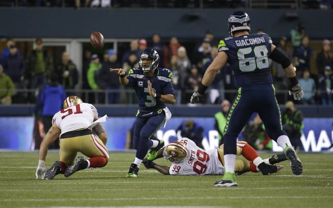 Seattle Seahawks' Russell Wilson throws the ball against the San Francisco 49ers  during the first half of the NFL football NFC Championship game Sunday, Jan. 19, 2014, in Seattle. (AP Photo/Ted S. Warren)