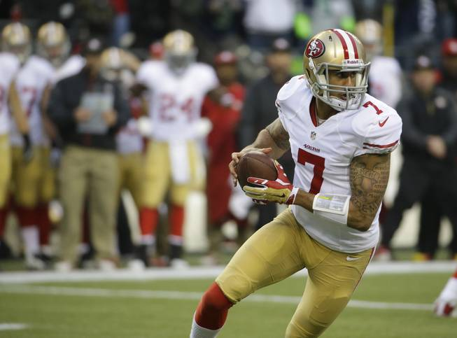San Francisco 49ers' Colin Kaepernick (7) works against the Seattle Seahawks during the first half of the NFL football NFC Championship game Sunday, Jan. 19, 2014, in Seattle. (AP Photo/Ted S. Warren)