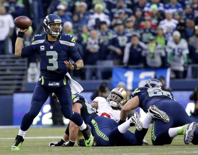 Seattle Seahawks' Russell Wilson throws during the first half of the NFL football NFC Championship game against the San Francisco 49ers Sunday, Jan. 19, 2014, in Seattle. (AP Photo/Ted S. Warren)
