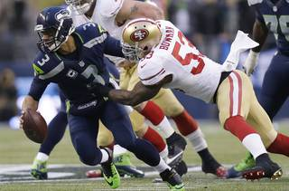 Seattle Seahawks' Russell Wilson is sacked by San Francisco 49ers' NaVorro Bowman (53) during the first half of the NFL football NFC Championship game Sunday, Jan. 19, 2014, in Seattle. (AP Photo/Marcio Jose Sanchez)