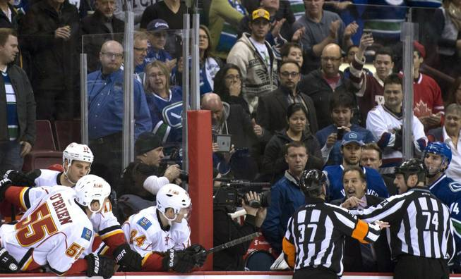 Referees get in the way of Vancouver Canucks head coach John Tortorella as he screams at the Calgary Flames bench during first period NHL hockey action at Rogers Arena in Vancouver, British Columbia Saturday Jan. 18, 2014.