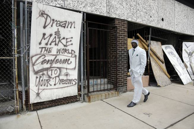 In this Thursday, Jan. 16, 2014 photo, Melvin White, founder of the Beloved Streets of America project, walks past a boarded up building during a tour of Dr. Martin Luther King Jr. Drive in St. Louis. The nonprofit is working to revitalize a downtrodden six-mile stretch of the drive named for the slain civil rights leader.