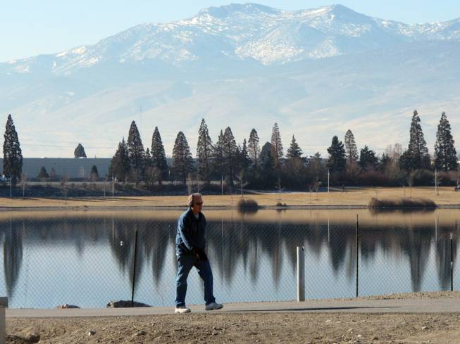 An unidentified man walks on the 2-mile loop trail surrounding the Sparks Marina, where all of the fish have died over the past month, on Friday, Jan. 17, 2014, in Sparks, Nev.