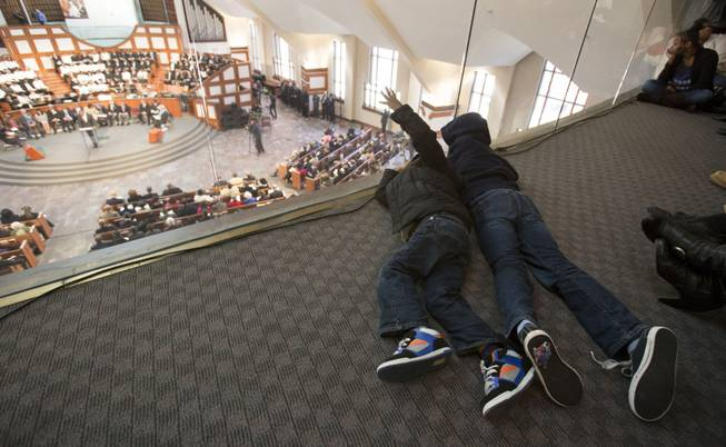 Brothers Lotanna, 6, left, and Kelo Ekwegbalu, 6, of Powder Springs, Ga., lay on the ground of the balcony during the Rev. Martin Luther King Jr. holiday commemorative service at Ebenezer Baptist Church Monday, Jan. 20, 2014, in Atlanta.