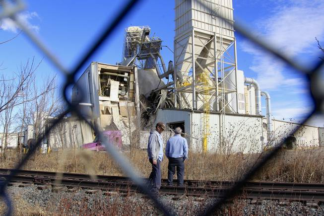 Two unidentified people with ties to the International Nutrition plant in Omaha, Neb., stand Monday, Jan. 20, 2014, outside the plant where a fire and explosion took place .