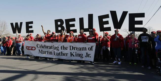 "Letters spelling ""We Believe"" are carried by a group during a march honoring Martin Luther King Jr., Monday,  Jan. 20, 2014, in San Antonio."