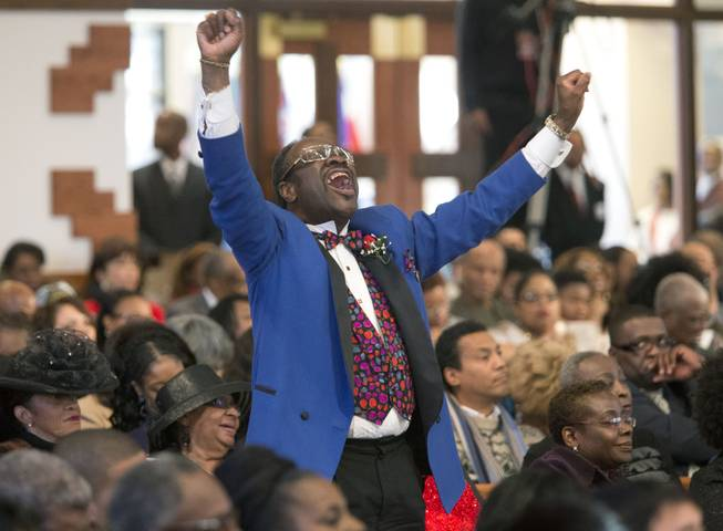 Elder Cal Murrell reacts to a speaker during the Rev. Martin Luther King Jr. holiday commemorative service at Ebenezer Baptist Church Monday, Jan. 20, 2014, in Atlanta. The service at the church where King preached featured prayers, songs, music and speakers.