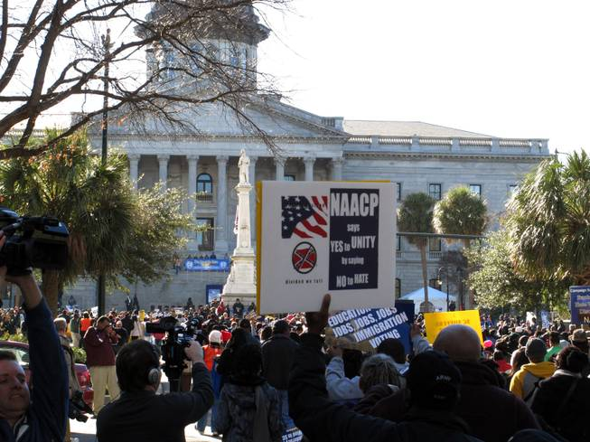 Marchers make their way to the South Carolina Statehouse during the King Day rally on Monday, Jan. 20, 2014, in Columbia, S.C. NAACP President William Barber told the crowd of a few thousand people that what conservatives leaders have done to the country is mighty low, but he thinks they are ready to find higher ground.