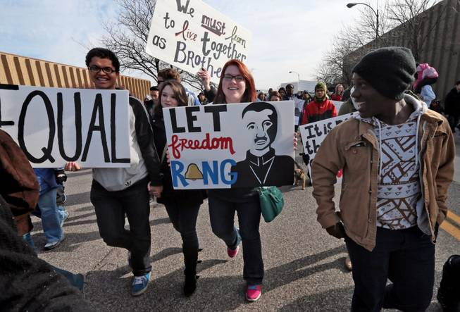 The message on the handmade signs of, from left, William Smith, Victoria Dowdy, and Stephanie Wormald, draw attention from a fellow marcher during the March of Celebration honoring the Rev. Martin Luther King Jr. on Monday, Jan. 20, 2014, in St. Louis.