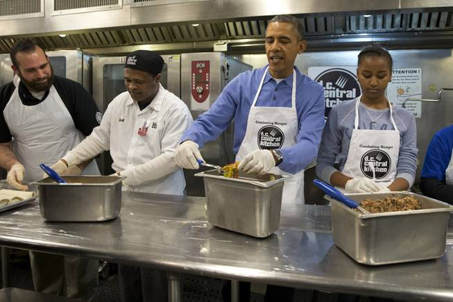 President Barack Obama and his daughter Sasha, right, make burritos at DC Central Kitchen as part of a service project in honor of Martin Luther King, Jr. Day,  Monday, Jan. 20, 2014, in Washington. Also helping were first lady Michelle Obama and daughter Malia Obama.