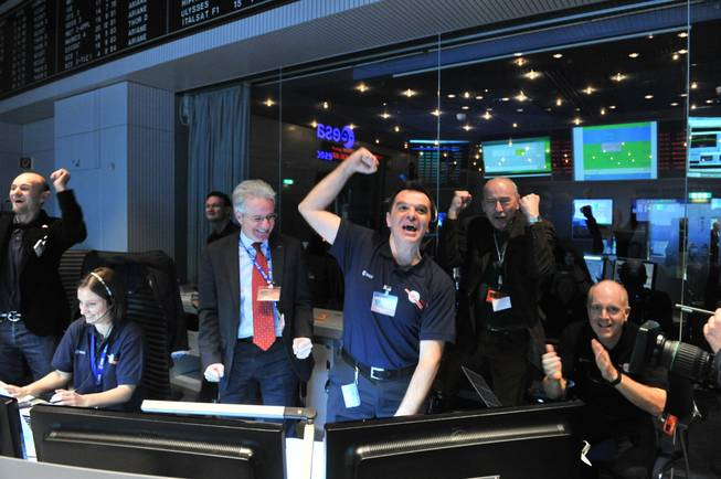 In this photo provided by the European Space Agency on Monday Jan. 20, 2014, technicians celebrate after receiving the Rosetta wake-up signal in the control room of ESA in Darmstadt, Germany.