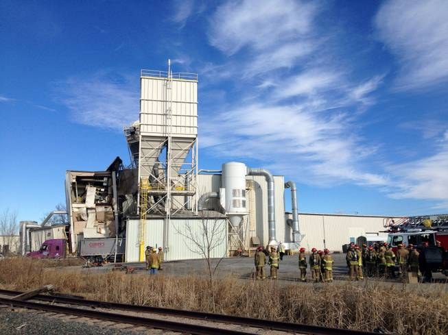 Firefighters stand outside the International Nutrition plant in Omaha, Neb., Monday, where a fire and explosion took place Jan. 20, 2014. At least nine people have been hospitalized and others could be trapped at the animal feed processing plant.