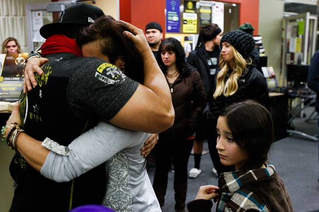Telmo Torres, left, hugs RiRi Whiting, both friends of Kelly Boren, during a memorial service and candlelight vigil for the Boren family at the Gold's Gym in Spanish Fork, Utah, on Saturday, Jan. 18, 2014. Authorities believe Joshua Boren, a police officer, shot and killed his wife, mother-in-law and two young children before turning the gun on himself.