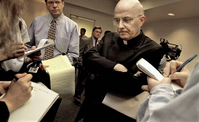 This April 17, 2002, file photo shows Chicago Cardinal Francis George listening to reporters' questions before he left for Rome to meet with Vatican officials and other American cardinals about the child sex abuse scandals in the United States.