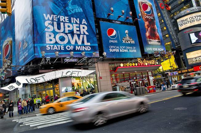 Large signs advertising the Super Bowl are seen on 42nd Street by Times Square, Monday, Jan. 20, 2014, in New York.