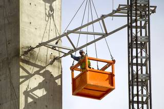 A worker removes scaffolding from the SkyVue observation wheel construction site on the Las Vegas Strip near Mandalay Bay Tuesday Jan. 21, 2014. David Gaffin, a Skyvue developer, wrote in an email that work is continuing on the project but that the scaffolding is not needed at this time.