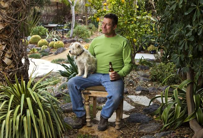 Horticulturalist Norm Schilling relaxes at the end of the day with Buckwheat his dog and a beer in one of his favorite backyard spots at their home on Tuesday, Jan. 21, 2014.