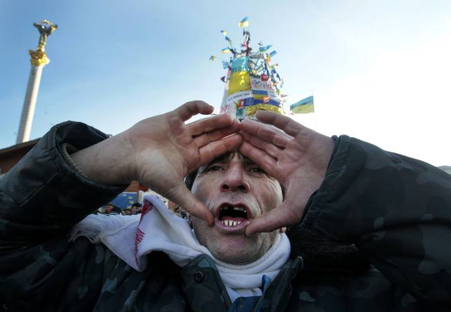 A pro-European Union activist shouts a slogan during a rally in Independence Square in Kiev, Ukraine, Sunday, Dec. 22, 2013. Protesters in Kiev are demanding President Viktor Yanukovych's resignation over his decision to ditch a pact with the European Union in favor of closer ties with Russia.