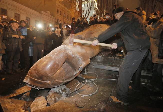 Ukrainian protesters smash a statue of Vladimir Lenin with a sledgehammer after toppling it, in central Kiev, Ukraine, Sunday, Dec. 8, 2013. The third week of protests continue Sunday with an estimated 200,000 Ukrainians occupying central Kiev to denounce President Viktor Yanukovychs decision to turn away from Europe and align this ex-Soviet republic with Russia.