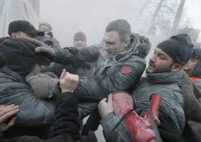 Opposition leader and former WBC heavyweight boxing champion Vitali Klitschko, center, is attacked and sprayed with a fire extinguisher as he tries to stop the clashes between police and protesters  in central Kiev, Ukraine, Sunday, Jan. 19, 2014. Hundreds of protesters on Sunday clashed with riot police in the center of the Ukrainian capital, after the passage of harsh anti-protest legislation last week seen as part of attempts to quash anti-government demonstrations. A group of radical activists began attacking riot police with sticks, trying to push their way toward the Ukrainian parliament building, which has been cordoned off by rows of police and buses.