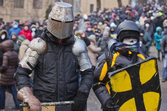 Protesters clad in improvised protective gear prepare for a clash with police in central Kiev, Ukraine, Monday, Jan. 20, 2014. After a night of vicious streets battles, anti-government protesters and police clashed anew Monday in the Ukrainian capital Kiev.