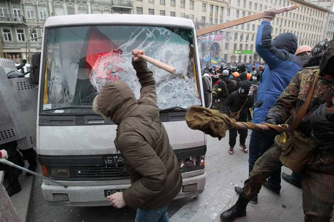 Protesters attack a riot police bus in central Kiev, Ukraine, Sunday, Jan. 19, 2014. Hundreds of protesters on Sunday clashed with riot police in the center of the Ukrainian capital, after the passage of harsh anti-protest legislation last week seen as part of attempts to quash anti-government demonstrations. A group of radical activists began attacking riot police with sticks, trying to push their way toward the Ukrainian parliament building, which has been cordoned off by rows of police and buses.