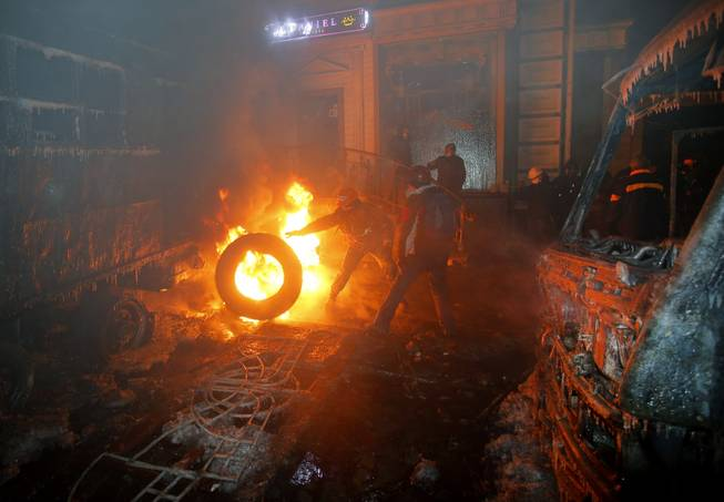 Protesters burn car tires as they clash with police in central Kiev, Ukraine, early Tuesday, Jan. 21, 2014. After a night of vicious street battles, anti-government protesters and police clashed again Monday in Ukraine's capital. Hundreds of protesters, many wearing balaclavas, hurled rocks and stun grenades. Police responded with tear gas.