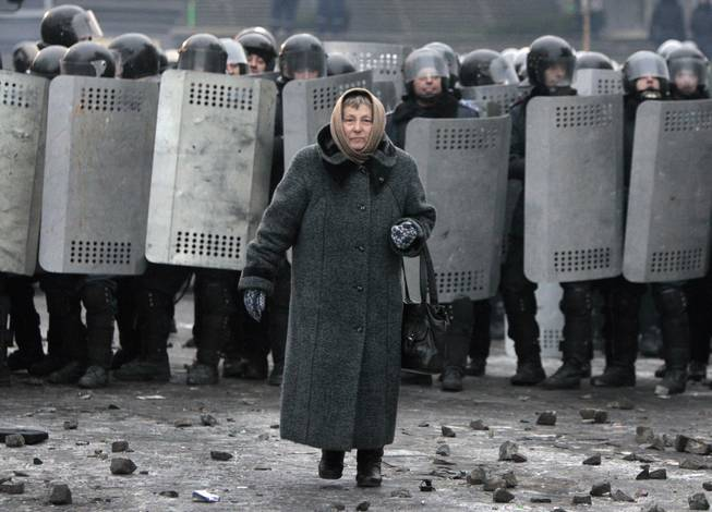 An elderly woman walks from police officers as they block a street during unrest in central Kiev, Ukraine,Tuesday, Jan. 21, 2014. Anti-government protesters have held their ground through a night of violent street clashes in the Ukrainian capital, despite police moving in to dismantle barricades erected in a street leading to government offices. Police attempted to move in on the protest camp early Tuesday, but faced fierce resistance from demonstrators who tossed fire bombs and stones in their direction.