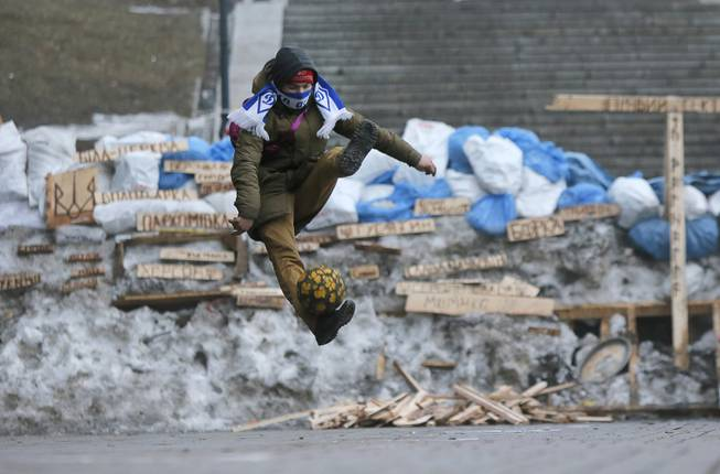 A Pro-European Union activist plays with the ball in front of barricades at the Independence Square in Kiev, Ukraine, Thursday, Dec. 19, 2013. President Vladimir Putin says Russia's $15-billion bailout for Ukraine is driven by a desire to help a partner in a desperate situation and isn't linked to its talks with the European Union.The Kremlin's move comes as Ukrainian President Viktor Yanukovych faces massive street protests over his decision to spike a pact with the EU in favor of closer ties with Russia.