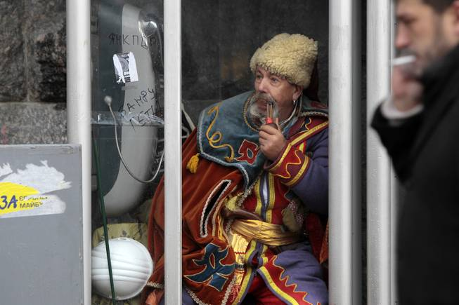 An anti-government protester sits in a telephone booth in Kiev, Ukraine, Friday, Dec. 6, 2013. A leader of the protests gripping Ukraines capital to try to force the governments resignation says the opposition is willing to talk with officials to find a way out of the crisis, but only if the police who violently dispersed demonstrators are punished.