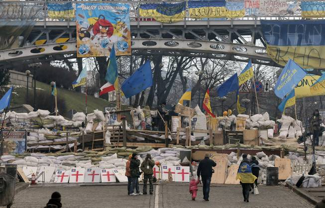 People walk past a barricade in Independence Square in Kiev, Ukraine, Monday, Dec. 23, 2013. Ukraine has been stricken with mass protests for over a month.  Protesters are demanding President Viktor Yanukovych's resignation over his decision to ditch a pact with the European Union in favor of closer ties with Russia.